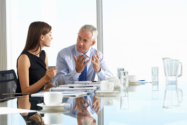 Two Business Colleagues Sitting Around Boardroom Table Having In